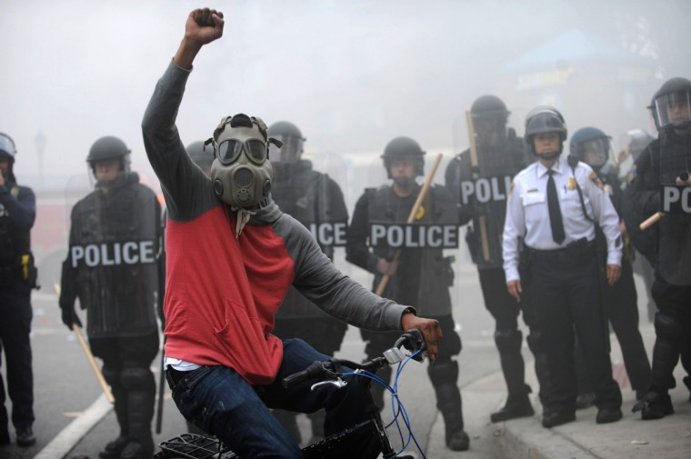 A protestor rides his bike in front of a police line at North and Pennsylvania Avenues after rioting and looting broke out throughout the city. (Algerina Perna/Baltimore Sun)