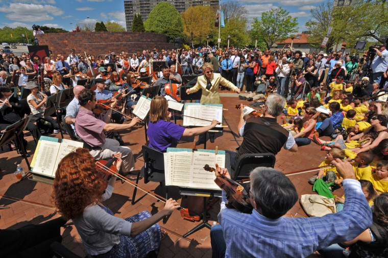 Conductor Marin Alsop, center,  with the BSO musicians during a free concert, organized by oboist Michael Lisicky, outside the Meyerhoff  at lunchtime on Wednesday. They wanted to offer an opportunity for all Baltimoreans to come together in the wake of the riot. The riot that followed Freddie Gray's burial has led to a curfew and the cancellation of some events. (Amy Davis/Baltimore Sun)