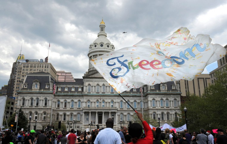 Kaeshawn Stewart of Baltimore waves a flag during Saturday's rally at War Memorial Plaza. (Jerry Jackson/Baltimore Sun)