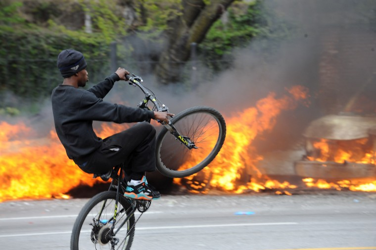 A cyclist does a wheelie in front of two burning police cars on at North Ave near Pennsylvania Avenue on the day of Freddie Gray's funeral.  (Algerina Perna/Baltimore Sun)