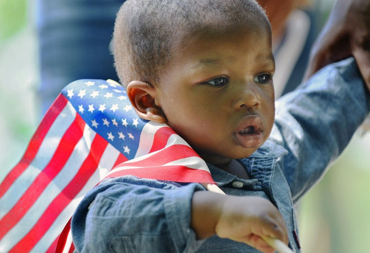 17-month-old Khamari Brown-Taborn hold a flag during the Memorial Day's Historic Fitzgerald Family cemetery ceremony, at the Maplewood Cemetery in Durham, N.C., Monday, May 25, 2015. (Bernard Thomas/The Herald-Sun via AP)