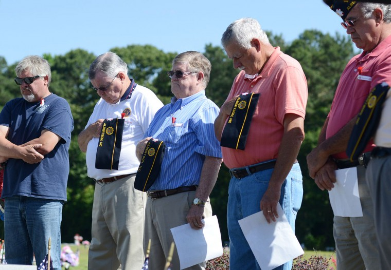 Veterans participate in a prayer for the families of the fallen during an American Legion Post 379 Memorial Day ceremony Monday, May 25, 2015, at Oak Ridge cemetery in Pink Hill, N.C. (Janet S. Carter/Daily Free Press via AP)