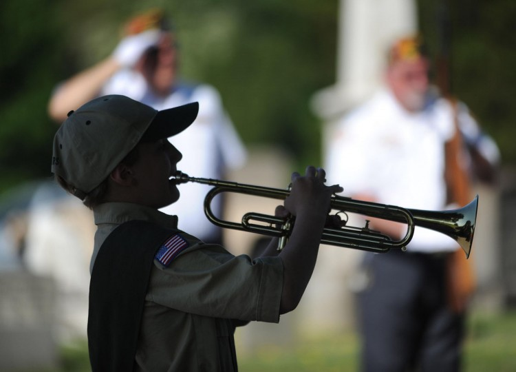 Sammy Suppes, 11, of Boy Scouts of America Troop 183, plays Taps during a Memorial Day service at Grandview Cemetery in Johnstown, Pa., Monday, May 25, 2015. (John Rucosky/The Tribune-Democrat via AP)