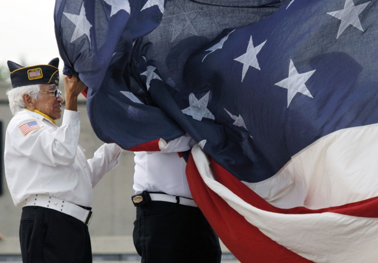 American Legion Color Guard member Roy Guzman helps hold the American flag at the Brownsville Veterans Park, Monday, May 25, 2015, in Brownsville, Texas. A one mile silent march concluded at the park where there was a flag raising ceremony, 21-gun salute and speeches to celebrate Memorial Day. (Brad Doherty/The Brownsville Herald via AP)