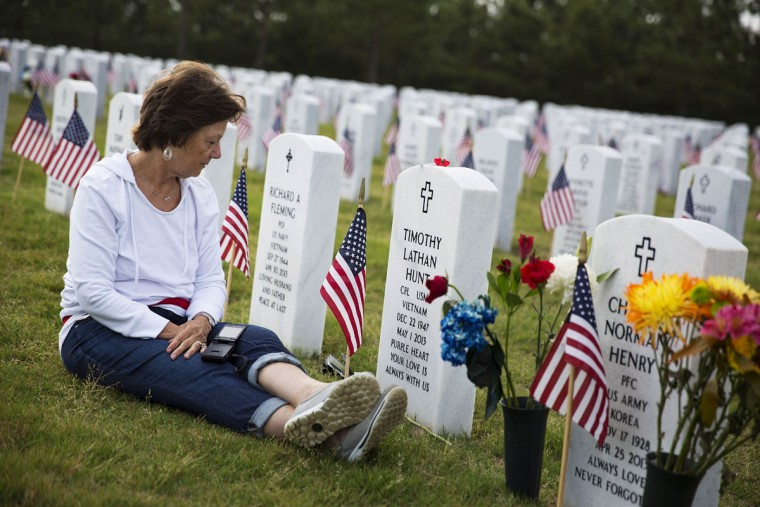 """Vickie Hunt sits next to the grave of her late husband, Vietnam veteran U.S. Marine Cpl. Timothy Hunt, at Georgia National Cemetery on Memorial Day, Monday, May 25, 2015, in Canton, Ga. """"I come every Memorial Day,"""" says Hunt. """"As soon as I go through the gates here it brings me a sense of peace."""" (AP Photo/David Goldman)"""