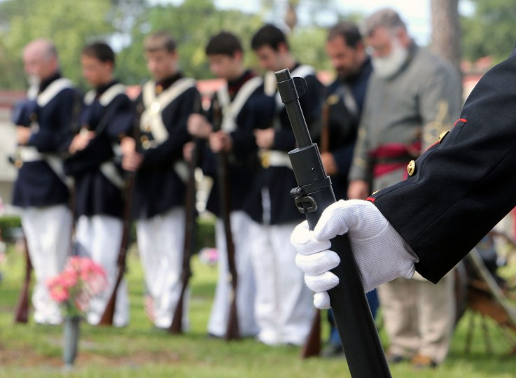 Members of the Gulf State Guards, Inc. pray during a Memorial Day Observance at Kent Forest Lawn Cemetery in Panama City, Fla. on Monday, May 25, 2015. (Andrew Wardlow/News Herald via AP)