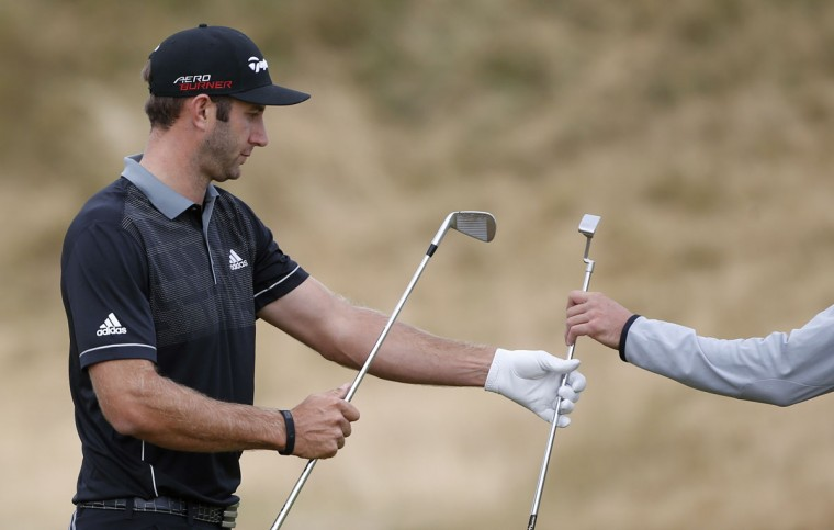 Dustin Johnson gets his putter from his caddie on the 11th hole during the first round of the U.S. Open golf tournament at Chambers Bay on Thursday, June 18, 2015 in University Place, Wash. (AP Photo/Lenny Ignelzi)