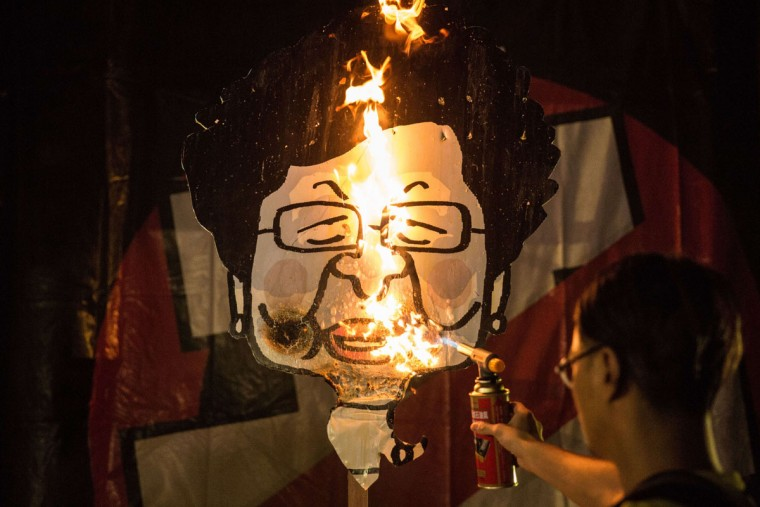 A pro-democracy activist from the Civic Passion group burns a placard representing deputy leader Carrie Lam during the commemoration of China's 1989 Tiananmen Square crackdown in the Tsim Sha Tsui district of Hong Kong late on June 4, 2015. Tens of thousands gathered to mark the 26th anniversary of China's Tiananmen Square crackdown, with the city deeply divided ahead of a vote on how to choose its next leader. (AFP Photo/Anthony Wallace)