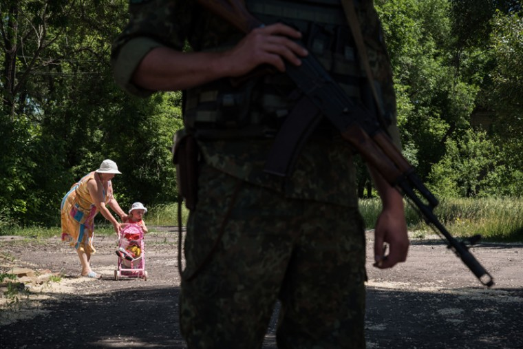 "A woman walks with her chilld as Ukrainian serviceman stands guard on Monday in Novotoshkivske village, Donetsk region, controlled by Ukrainian forces on the frontline with pro-Russian separatists. World leaders at a G7 summit in Germany were on Monday set to present a united front against global security threats ranging from jihadist insurgencies to what U.S. President Barack Obama condemned as ""Russian aggression in Ukraine."" (SERGEY POLEZHAKA/AFP/Getty Images)"