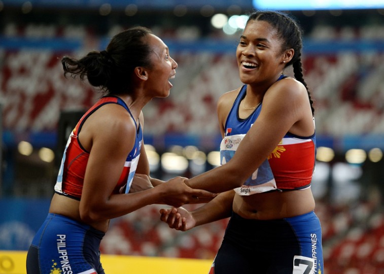 Kayla Anise Richardson (R) of the Philippines celebrates with comptariot Princess Joy Griffey (L) after winning the women's 100m final during the 28th Southeast Asian Games in Singapore on Tuesday. (MANAN VATSYAYANA/AFP/Getty Images)