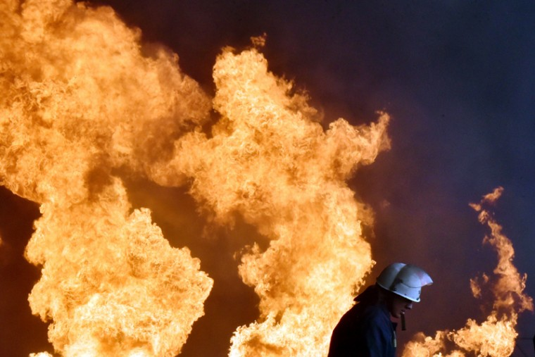 A Ukrainian firefighter stands in front of flames as he works to extinguish a fire at a fuel depot  in the  village of Kryachki, some 18 miles southwest from Kiev, on Tuesday. Ukraine urgently evacuated hundreds of residents on Tuesday from the site of a series of fuel depot blasts near Kiev that set off a ferocious fire and left several people missing and at least one confirmed dead. The defense ministry said it was also taking emergency measures to prevent the flames from engulfing a nearby military airbase which has MiG-29 fighter jets and munitions on site.  (SERGEI SUPINSKY/AFP/Getty Images)