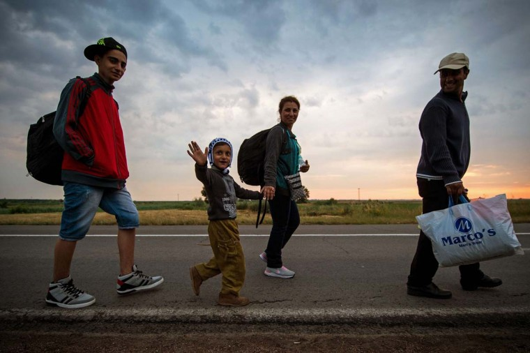 A boy waves as migrant walk towards the border with Hungary, near the northern Serbian town of Kanjiza, on June 25, 2015. Hungary on June 25 reversed its decision to suspend a key EU rule on processing asylum claims, a day after its announcement caused concern in Brussels and elsewhere. Illegal immigrants cross Serbia on their way to other European countries as it has land access to three members of the 28-nation bloc -- Romania, Hungary and Croatia. The number of immigrants entering Hungary rose from 2,000 in 2012 to 54,000 this year so far. According to official figures, 95 percent of them arrive from Serbia.   || CREDIT: ANDREJ ISAKOVIC - AFP/GETTY IMAGES