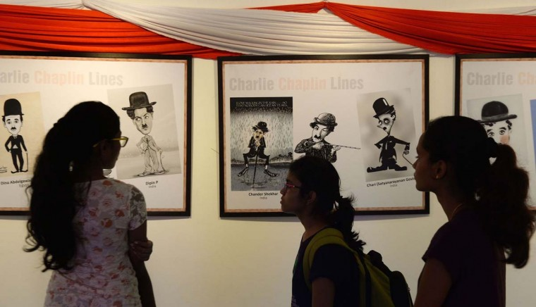 Indian youth look at an exhibition of cartoons and caricatures of Charlie Chaplin in Mumbai on June 26, 2015. Two hundred cartoonists across the world showcased their work.   || CREDIT: PUNIT PARANJPE - AFP/GETTY IMAGES