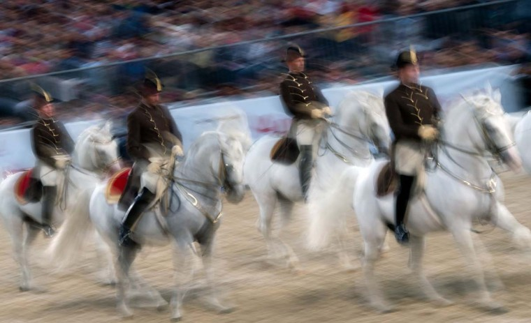 This long exposure picture shows Equestrians of Vienna's Spanish Horse Riding School participating in their public gala-rehearsal in front of the Hofburg palace at Helden square in Vienna, Austria on June 25, 2015. The School celebrates its 450th birthday on June 26, 2015.  || CREDIT: JOE KLAMAR - AFP/GETTY IMAGES