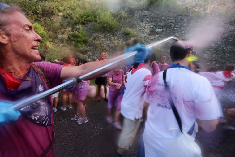 """A man sprays red wine on revelers during the""""Batalla del Vino"""" (Battle of Wine) in Haro, on June 29, 2015. (CESAR MANSO/AFP/Getty Images)"""