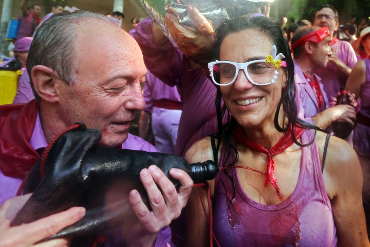 """A man uses a wineskine to pour red wine on a woman's chest during the""""Batalla del Vino"""" (Battle of Wine) in Haro, on June 29, 2015. (CESAR MANSO/AFP/Getty Images)"""