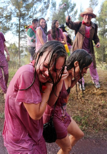 """A man sprays red wine on two girls during the""""Batalla del Vino"""" (Battle of Wine) in Haro, on June 29, 2015. (CESAR MANSO/AFP/Getty Images)"""