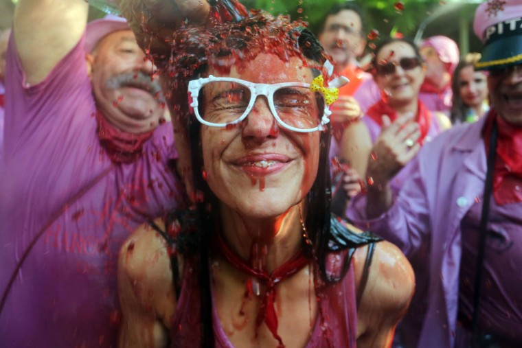 """A man pours red wine on a woman's head during the """"Batalla del Vino"""" (Battle of Wine) in Haro, on June 29, 2015. (CESAR MANSO/AFP/Getty Images)"""