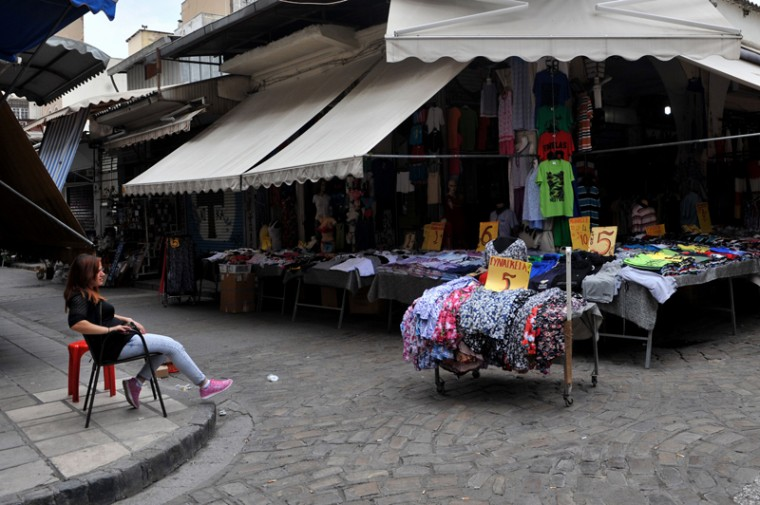 A saleswoman sits as she waits for customers in Thessaloniki on Tuesday. Greece requested a two-year rescue deal with the European Union to save the crisis-hit country, just hours before its international bailout expires. (SAKIS MITROLIDIS/AFP/Getty Images)