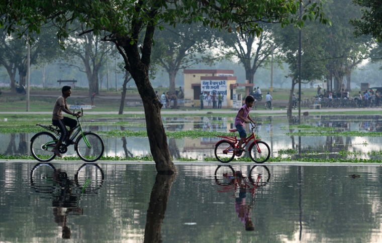 Indian children ride bicycles along a flooded pathway following heavy rain in Allahabad on Tuesday. (Sanjay Kanojia/AFP/Getty Images)