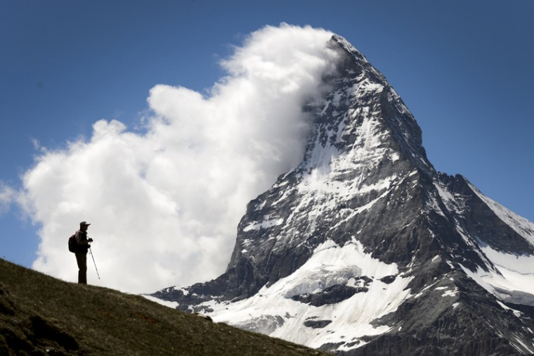 A tourist is seen in silhouette in front of the Matterhorn mountain on Tuesday in Riffelalp above Zermatt. The alpine resort celebrates this year the 150 anniversary of Matterhorn's first climb. (FABRICE COFFRINI/AFP/Getty Images)