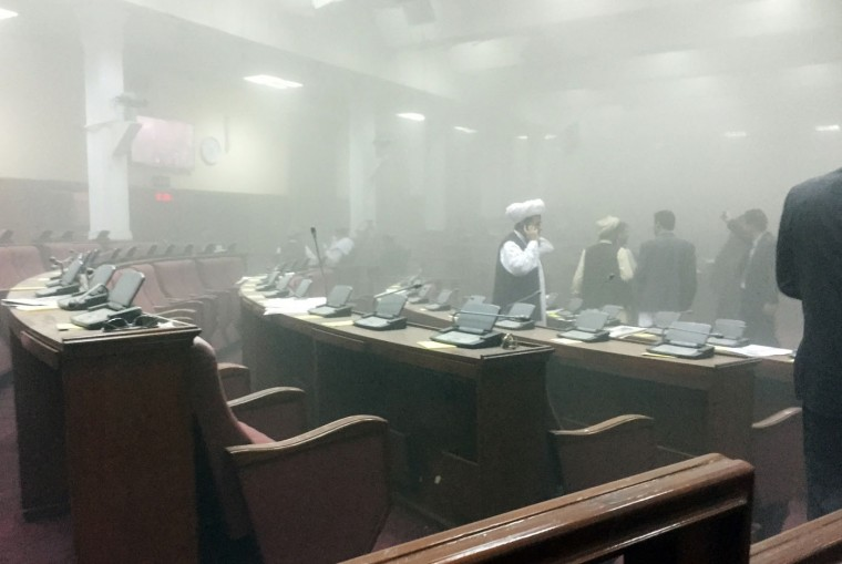 In this photo taken by Dr. Naqibullah Faiq, an Afghan member of parliament, lawmakers leave the main hall after a suicide attack in front of the main gate of Parliament, during clashes with Taliban fighters in Kabul, Afghanistan, Monday, June 22, 2015. The Taliban launched a complex attack, with a suicide car bomber striking at the entrance and gunmen battling police as lawmakers were meeting inside to confirm the appointment of a defense minister, police and witnesses said. (Dr. Naqibullah Faiq via AP)