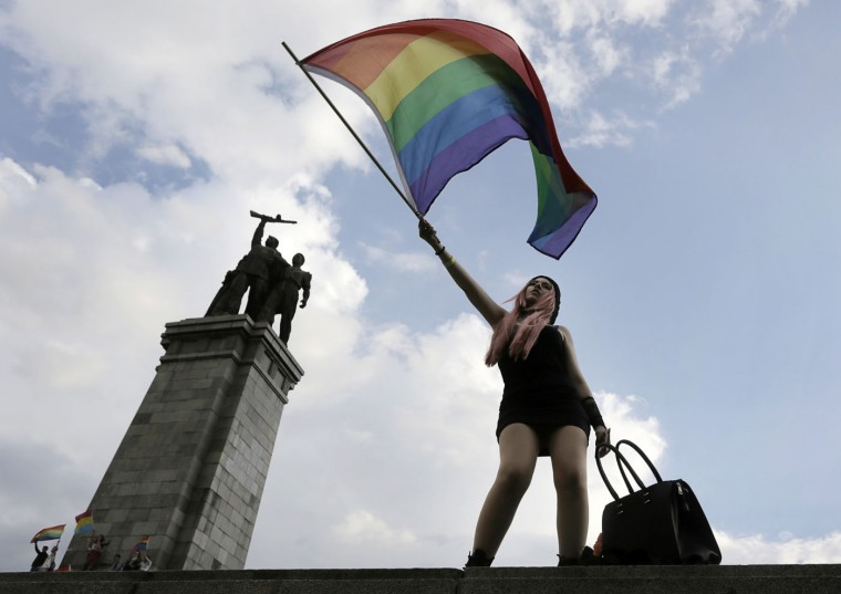 An activist waves a rainbow flag in front of the Monument of the Soviet Army, during the Sofia Gay Pride Parade in Sofia, Saturday, June 27, 2015. Hundreds paraded through the Bulgarian capital of Sofia under rainbow-colored balloons and banners for that city's eighth Gay Pride march on Saturday. They were flanked by police in the wake of calls by some extremist groups to stop the rally. (AP Photo/Valentina Petrova)