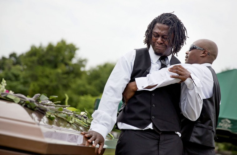 Brandon Risher, left, is pulled away by a friend as he cries over the casket of his grandmother, Ethel Lance, following her burial service, Thursday, June 25, 2015, in Charleston, S.C. Lance was one of the nine people killed in the shooting at Emanuel AME Church last week in Charleston. (AP Photo/David Goldman)