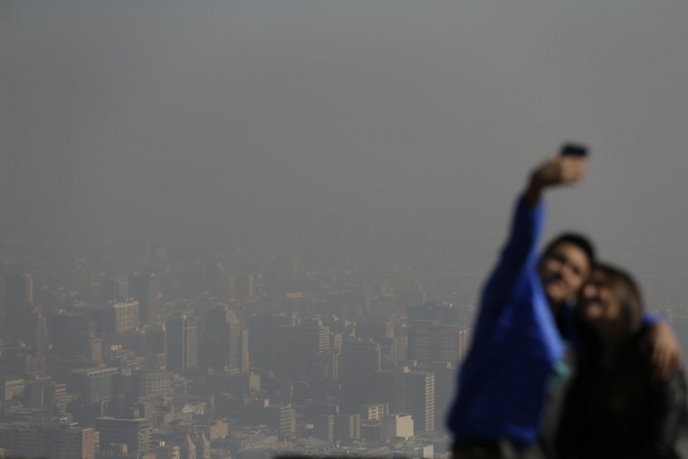 """Tourists take pictures of themselves from the """"Cerro San Cristobal"""" with a view behind them of smog filled downtown Santiago, Chile, Monday, June 22, 2015. Authorities declared an environmental emergency Monday because of high levels of pollution in the air. (AP Photo/Jorge Saenz)"""