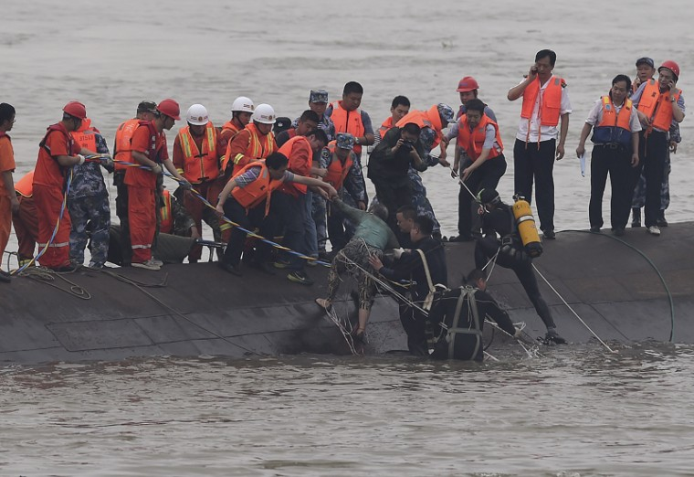 In this photo released by China's Xinhua News Agency, rescuers save a survivor, center, from the overturned passenger ship in the Jianli section of the Yangtze River in central China's Hubei Province on Tuesday. Rescuers pulled several survivors to safety after hearing cries for help from inside a capsized cruise ship that went down overnight in a storm on China's Yangtze River, state broadcaster CCTV said. (Cheng Min/Xinhua via AP)