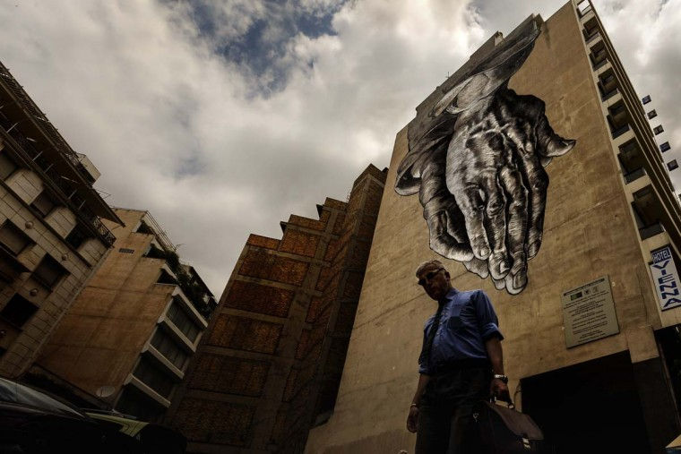 "A man walks down a street with a turned upside down mural inspired by ""The Praying Hands"" by artist of the Renaissance Albrecht Durer, in Athens, Friday, June 26, 2015. The bitter standoff between Greece and its international creditors was extended into the weekend, just days before Athens has to meet a crucial debt deadline which could decide whether it goes bankrupt and gets kicked out of the euro currency club.  