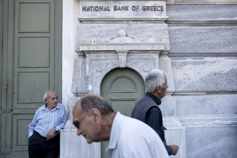 Elderly people wait to receive their pension outside the National bank of Greece headquarters in Athens, Monday, June 29, 2015. Anxious Greek pensioners swarmed bank branches hoping to be able to receive their pensions Monday and others lined up at ATMs as they gradually began dispensing cash again on the first day of capital controls imposed in a dramatic twist in Greece's five-year financial saga. (AP Photo/Petros Giannakouris)