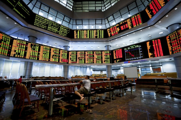 Malaysian men watch the trading board at a private stock market gallery in Kuala Lumpur, Malaysia, Monday, June 29, 2015. Asian stock markets sank Monday after Greece closed its banks and imposed capital controls in a dramatic turn in its struggle with heavy debts. (AP Photo/Vincent Thian)