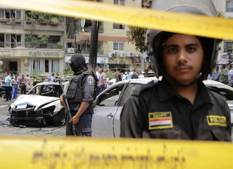 Egyptian policemen stand guard after a bomb attack that targeted Egypt's prosecutor general in the Heliopolis district of Cairo, Egypt, Monday, June 29, 2015. An official says Monday's attack targeted Hisham Barakat's convoy, wounding two security guards and a civilian. The official says it's not yet clear if Barakat was hurt or not. (AP Photo/Amr Nabil)