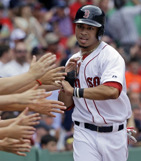 Fans reach out to congratulate Boston Red Sox's Mookie Betts after he scored on a double by Xander Bogaerts in the seventh inning of a baseball game against the Baltimore Orioles at Fenway Park, Thursday, June 25, 2015, in Boston. (AP Photo/Elise Amendola)