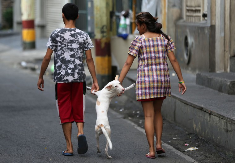 Filipinos walk beside their dog in the walled city of Intramuros, in Manila, Philippines on Thursday, June 4, 2015. (AP Photo/Aaron Favila)