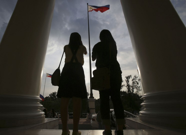 Filipino students stand in front of a Philippine flag outside the National Museum in Manila, Philippines, Thursday, June 11, 2015. The country marks it's 117th Independence Day on June 12. (AP Photo/Aaron Favila)