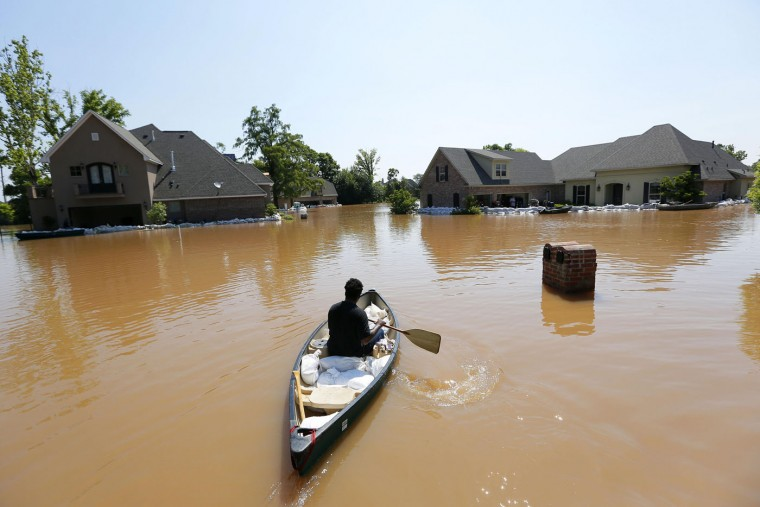 Troy Boyd transports sandbags to a house that is trying to protect itself from water caused by the flooding of the Red River, Thursday, June 11, 2015, in Shreveport, La. Flooding from the swelling river put hundreds of homes and farmland underwater or in danger in rural northwest Louisiana, and state officials said Thursday that they would seek a federal disaster declaration to get help for residents. (AP Photo/Jonathan Bachman)