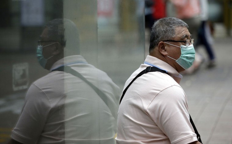 A man wearing a mask as a precaution against Middle East Respiratory Syndrome (MERS) takes a rest at a shopping district in Seoul, South Korea, Thursday, June 11, 2015. Experts from the World Health Organization and South Korea on Wednesday urged the reopening of more than 2,700 schools closed over fears of the deadly MERS virus. (AP Photo/Lee Jin-man)