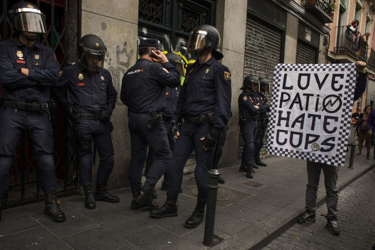 "Riot police stand guard as a man display a banner reading ""Love Paito, hate cops"" as activists gather to protect a four story occupied building in Madrid, Spain, Thursday, June 11, 2015. Hundreds of activists and squatters occupied a four storey building in spite of dozens of riot police cordon the area. Early today the group of squatters called ""Patio Maravilla"" have been evicted from a previous building that was working as cultural centre. (AP Photo/Andres Kudacki)"