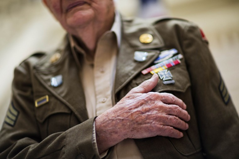 World War II veteran Robert Harris, 90, of Fort Valley, Ga., places his hand on his chest during the singing of the National Anthem at a ceremony where Harris and nine fellow WWII veterans were awarded the French Legion of Honor by the Consul General of France, Thursday, June 4, 2015, in Atlanta. The Legion of Honor is the highest distinction France can award to a citizen or foreigner. The veterans honored fought on French territory as part of the liberation of the country from Nazi Germany and were nominated by President Francois Hollande. Harris was a squad leader and rifleman in the infantry and participated in campaigns in the Ardennes, the Rhineland and Central Europe. (AP Photo/David Goldman)