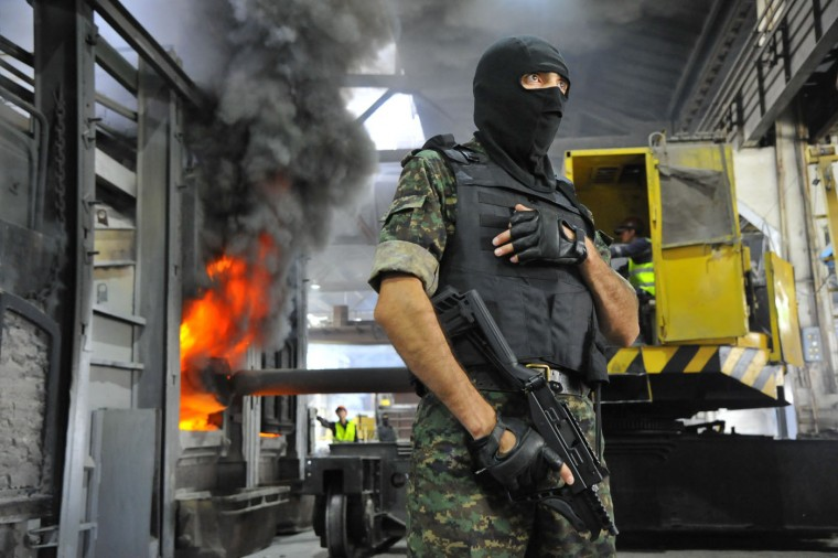 An Uzbekistan National Security Service officer stands guard, as drugs are burnt behind him, at a plant on the outskirts of Tashkent, Uzbekistan's capital, Thursday, June. 25, 2015. Drug trafficking is on rise in Uzbekistan as Afghanistan significantly expanded opium growing areas. (AP Photo/ Anvar Ilyasov)