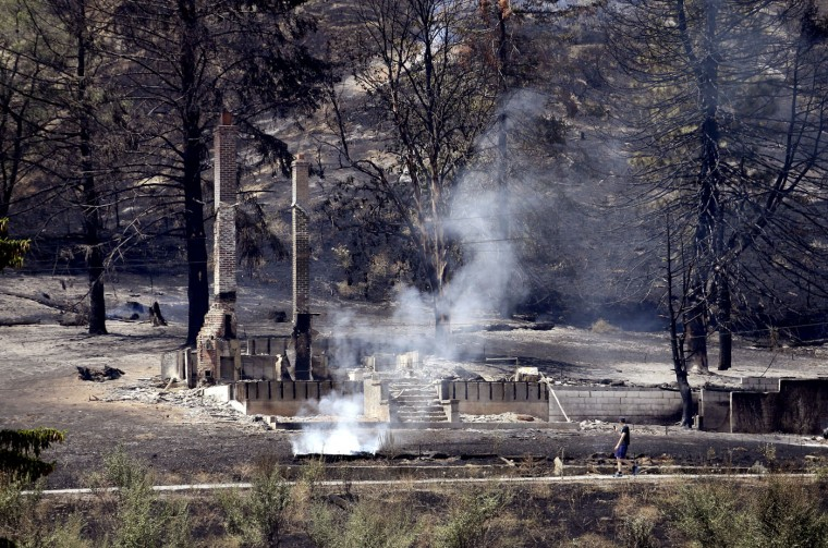 The foundation and chimneys from a destroyed home continue to smolder following a wildfire the night before, Monday, June 29, 2015, in Wenatchee, Wash. The wildfires hit parts of central and eastern Washington over the weekend as the state is struggling with a severe drought, destroying dozens of structures and forcing hundreds to flee. (AP Photo/Elaine Thompson)