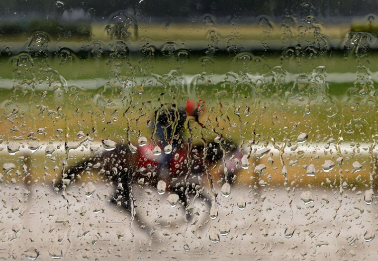Rain water coats the window of an observation tower as an exercise rider guides a horse around the main track at Belmont Park on Tuesday. Kentucky Derby and Preakness Stakes winner American Pharoah will try for a Triple Crown on Saturday in the Belmont Stakes horse race. (Julie Jacobson/AP)
