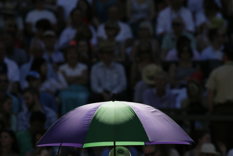Sun rays fall on an umbrella during a break in the singles first-round match between Andy Murray of Britain and Mikhail Kukushkin of Kazakhstan at the All England Lawn Tennis Championships in Wimbledon, London, on Tuesday. (Tim Ireland/AP)