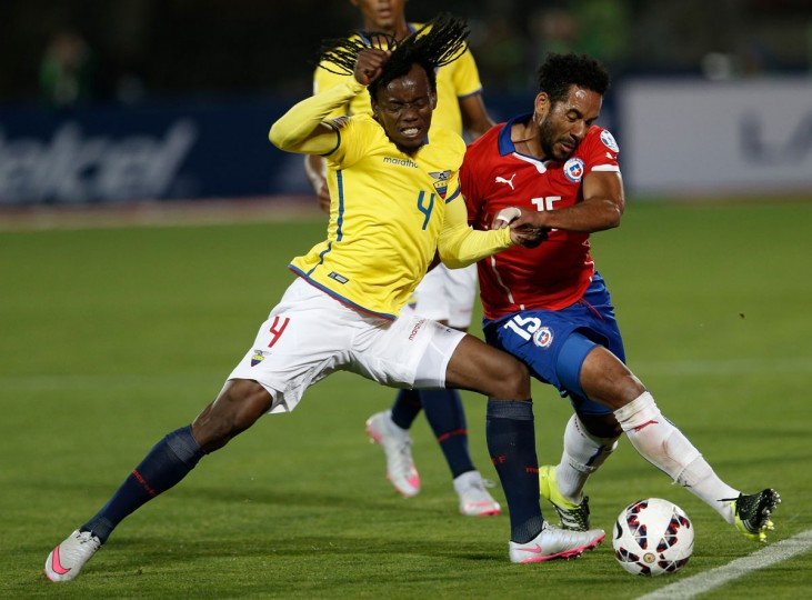 Ecuador's Juan Carlos Paredes, left, fight for the ball with Chile's Jean Beausejour during a Copa America Group 1 soccer match at the National Stadium in Santiago, Chile, Thursday, June 11, 2015.(AP Photo/Silvia Izquierdo)