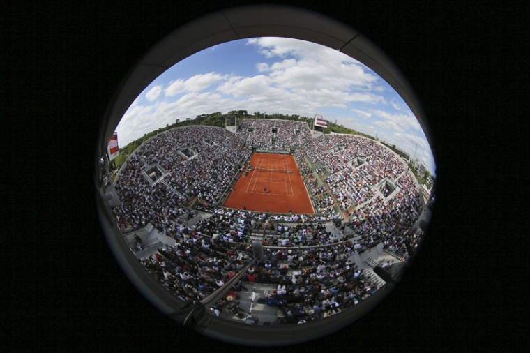 In this image taken with a circular fisheye lens, Switzerland's Roger Federer plays the quarterfinal match of the French Open tennis tournament against Switzerland's Stan Wawrinka on Suzanne Leglen court at the Roland Garros stadium, in Paris on Tuesday. (David Vincent/AP)