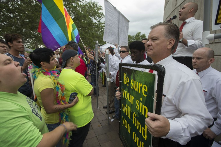 Anti-gay marriage protestors picket at the Cincinnati Pride festival at Riverside Park, Saturday, June 27, 2015, in Cincinnati. On Friday, the U.S. Supreme Court ruled that same-sex couples have the right to marry nationwide. (AP Photo/John Minchillo)