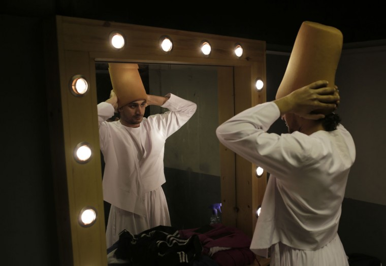 "In this Thursday, April 23, 2015 photo, whirling dervish Mahmoud Rizk, a member of the Al-Tannoura Egyptian Heritage Dance Troupe, adjusts his ""sikke,"" a brown tall felt cap made of camel wool, backstage before a performance, at the ?El Sawy cultural center in Cairo, Egypt. The Whirling Dervishes art form draws its roots from the ecstatic movements of Sufi Muslim mystics seeking a state of delirious oneness with God. Religious devotion is at the heart of almost everything. The spinning of the dervish dancers is partially meant to symbolize the way Muslim pilgrims performing the Hajj pilgrimage ritually circle the cube-shaped Kabaa in Mecca, Saudi Arabia. (AP Photo/Amr Nabil)"