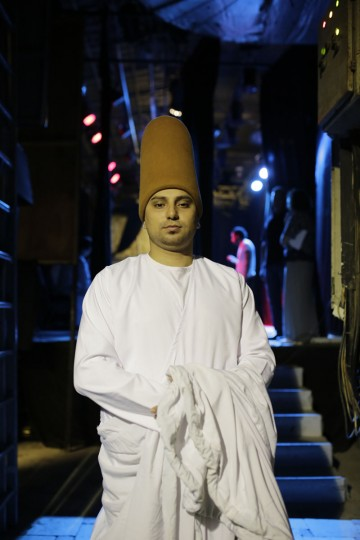 "In this Thursday, May 28, 2015 photo, whirling dervish Ali Taha, a member of the Al-Tannoura Egyptian Heritage Dance Troupe, poses for a photograph backstage before a performance, at the ?El Sawy culture center, in Cairo, Egypt. The dancers earn between 100 and 250 Egyptian pounds (between $13 and $32) per performance. But many of them describe it as far more than just a job. ""I'm ready to dance for free, especially with the Mawlawiyah dervishes,î said Taha. ìWhile whirling I feel like a white bird flying in the sky."" (AP Photo/Amr Nabil)"